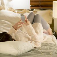 ベッドに寝転びスマートフォンを見る女性