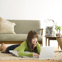 床に寝転びノートパソコンを操作する女性