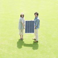 ソーラーパネルを持ち微笑むカップル