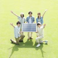 ソーラーパネルを持ち微笑む若者たち