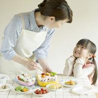 キャラクター弁当を作る母親と微笑む女の子