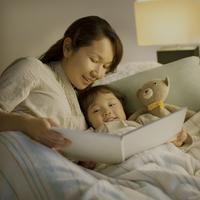 ベッドで絵本の読み聞かせをする親子