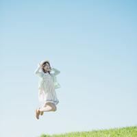草原でジャンプをする女性