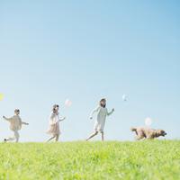 草原を走る3人の女性と犬