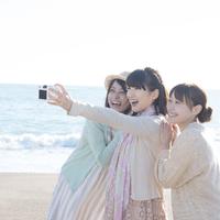 海で写真を撮る3人の女性