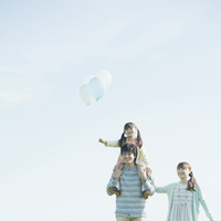 風船を持ち肩車をする親子