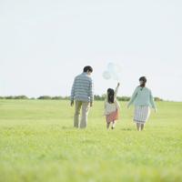 草原で風船を持ち歩く親子の後姿