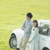 車に寄りかかり微笑むカップル