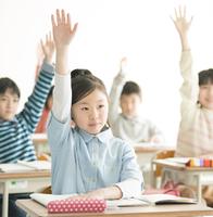 教室で手を挙げる小学生