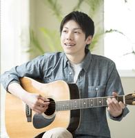 リビングでギターを弾く男性