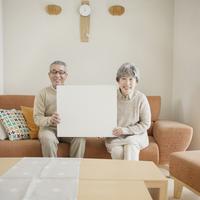 ソファに座りメッセージボードを持つシニア夫婦