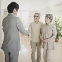 ビジネスマンと握手をするシニア夫婦