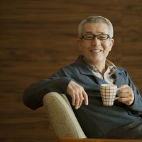 コーヒーカップを持ち微笑むシニア男性