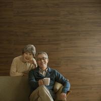 ソファで微笑むシニア夫婦