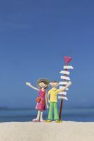 海辺の道しるべで手を挙げる夫婦と青空 クラフト