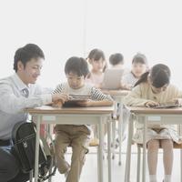 タブレットPCで勉強をする小学生と先生