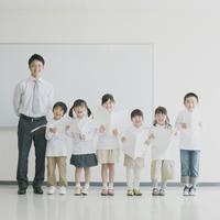 楽譜を持ち微笑む小学生と先生