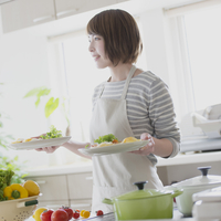 キッチンで料理を持ち微笑む女性