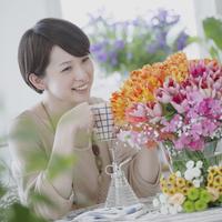 花を見ながらコーヒーを飲む女性