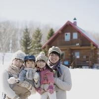 ログハウスの前で微笑む家族
