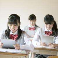 タブレットPCを持ち授業を受ける中学生