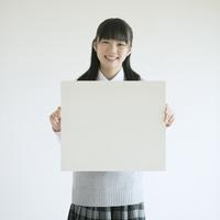 ホワイトボードを持ち微笑む中学生