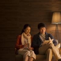 ソファーに座りくつろぐミドル夫婦