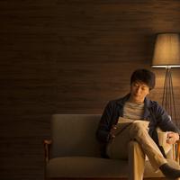 ソファーに座り本を読むミドル男性