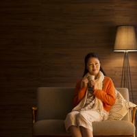 ソファーに座りコーヒーを飲むミドル女性