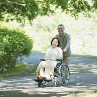 車椅子で散歩をするシニア夫婦