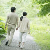 公園を散歩するミドル夫婦の後姿