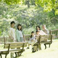 公園で微笑む3世代家族
