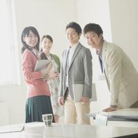オフィスで微笑むビジネスマンとビジネスウーマン