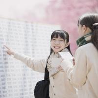 合格発表のボードを見て喜ぶ女子中学生