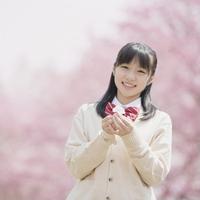 桜の花を持ち微笑む女子中学生