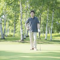 ゴルフクラブを持ち微笑む男性