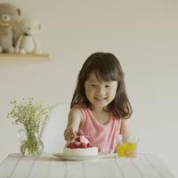 ケーキのイチゴを取ろうとする女の子 11017014879| 写真素材・ストックフォト・画像・イラスト素材|アマナイメージズ