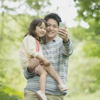 新緑の中でスマートフォンの画面を見る親子