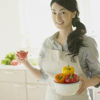 キッチンで野菜を持ち微笑む女性