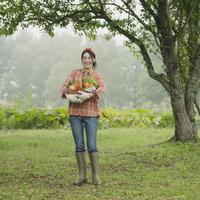 農園で野菜を持ち微笑む女性