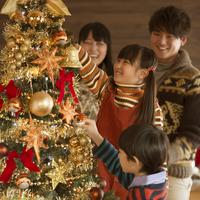 クリスマスツリーに飾り付けをする親子