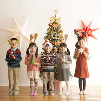 クリスマスツリーの前に並ぶ子供達
