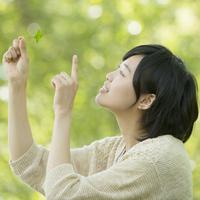 新緑の中で四葉のクローバーを持ち微笑む女性