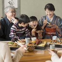 おせち料理を食べる3世代家族