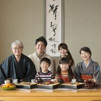 テーブルの上に並ぶおせち料理と微笑む3世代家族