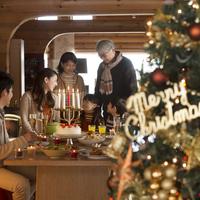クリスマスパーティーをする3世代家族とクリスマスツリー