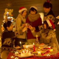 パーティー料理とクリスマスパーティーをする若者たち