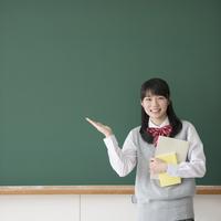黒板の前で微笑む女子校生