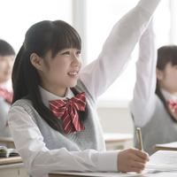 教室で手を挙げる女子校生