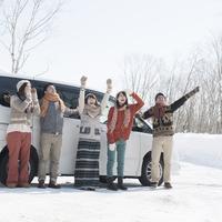 車の前で微笑む若者たち